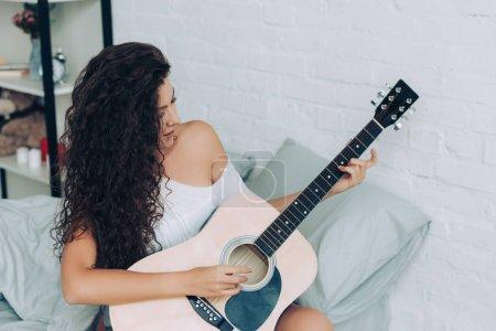 Foto de Niña rizada sonriente tocando en la guitarra acústica en dormitorio en casa - Imagen libre de derechos