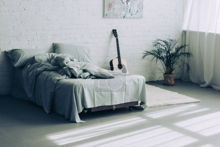 interior of modern bedroom with guitar and houseplant