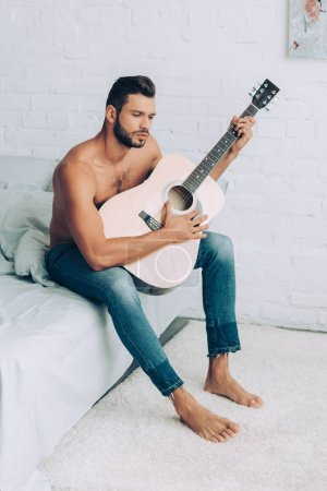 muscular shirtless man in jeans playing on acoustic guitar during morning time in bed at home