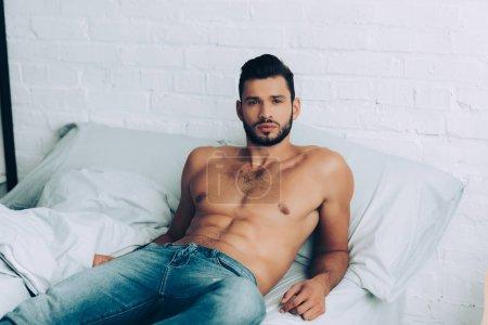 Photo pour Bel homme torse nu musclé en jeans posant sur le lit à la maison - image libre de droit