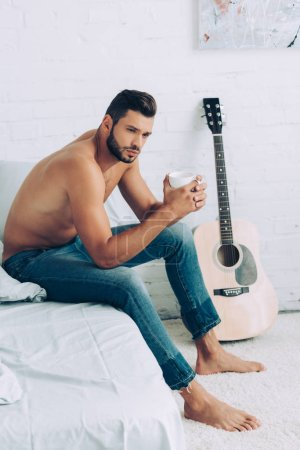 handsome shirtless man in jeans drinking coffee cup during morning time in bedroom at home