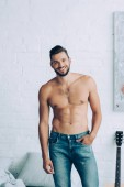 smiling shirtless man with muscular torso posing in bedroom at home
