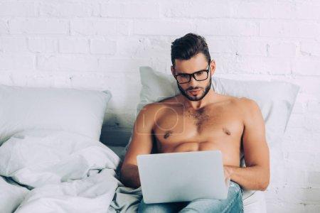 Photo pour Beau torse nu freelance masculin avec torse musclé travaillant sur ordinateur portable dans le lit à la maison - image libre de droit