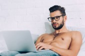 muscular shirtless male freelancer in eyeglasses working on laptop in bed at home