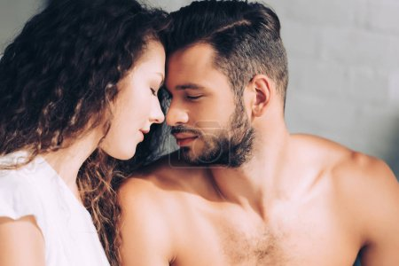 side view of young couple with closed eyes sitting face to face