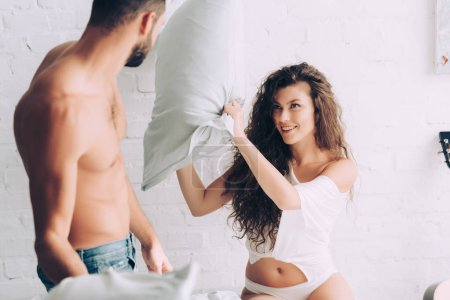 partial view of shirtless muscular man having pillow fight with happy girlfriend in bedroom at home