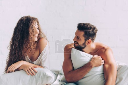 laughing young couple laying on bed with pillows in bedroom at home