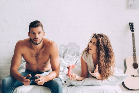 Photo for Irritated young woman gesturing by hand while her concentrated boyfriend playing video game by joystick - Royalty Free Image