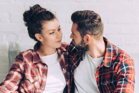 joyful young woman in checkered shirt embracing boyfriend at home