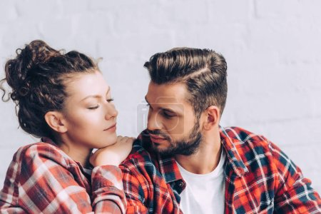 pretty young woman in checkered shirt embracing boyfriend at home