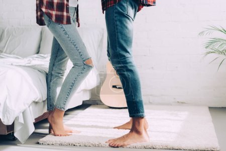 partial view of couple in jeans standing next to each other in bedroom at home