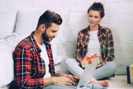 Photo for Happy male freelancer working on laptop and his girlfriend sitting with present box at home - Royalty Free Image