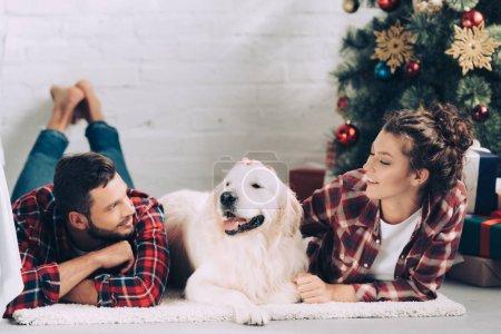 Photo pour Mise au point sélective du mignon golden retriever entre heureux jeune couple sur Noël à la maison - image libre de droit