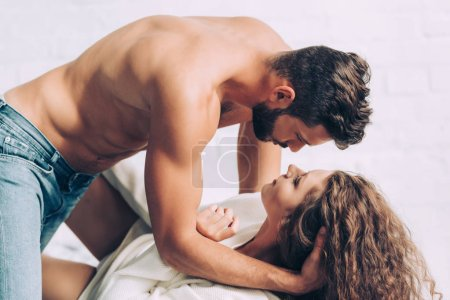 Photo for Side view of shirtless handsome man laying on beautiful curly girlfriend in bedroom at home - Royalty Free Image