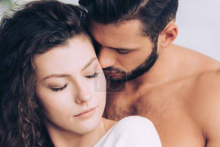 Photo pour Bel homme baiser belle copine bouclée, posant avec les yeux fermés - image libre de droit