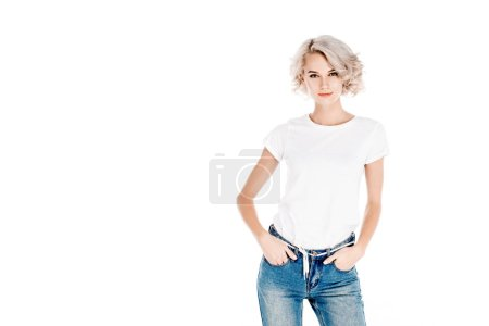 Attractive blonde young adult woman with hands in pockets isolated on white