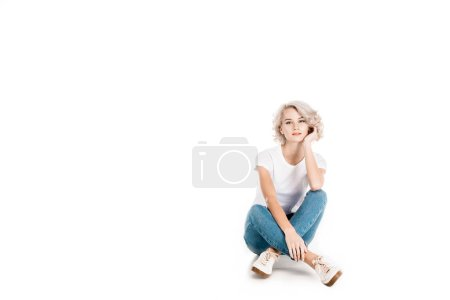 Attractive blonde young adult woman sitting isolated on white