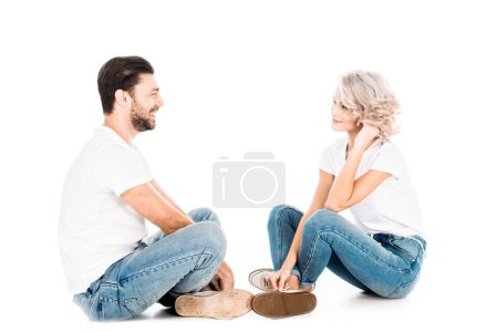 Wonderful couple looking at each other while sitting isolated on white