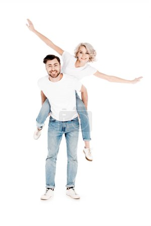 Happy wonderful couple having fun while man piggybacking blonde woman isolated on white