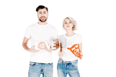 Wonderful agoung adult couple holding signs love  while looking at camera isolated on white