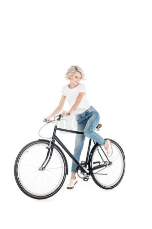 Beautiful young adult woman riding bicycle isolated on white