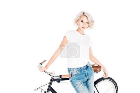 Attractive serious woman standing while leaning to bicycle isolated on white