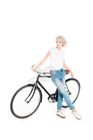 Photo pour Magnifique femme blonde penchée à vélo isolé sur blanc - image libre de droit
