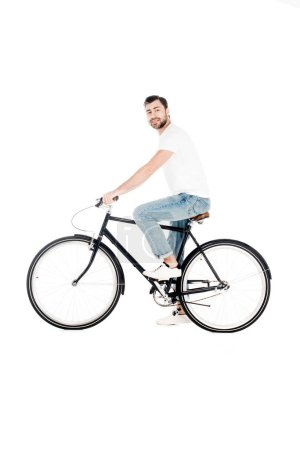 Handsome smiling young adult riding bicycle while looking at camera isolated on white