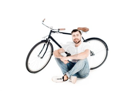 Handsome smiling young adult man sitting near bicycle isolated on white