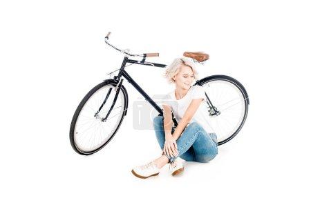 Photo pour Magnifique blonde jeune adulte femme assise près de la bicyclette isolée sur blanc - image libre de droit