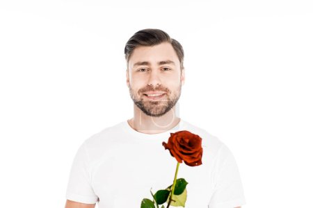 Handsome smiling young adult man with red rose isolated on white