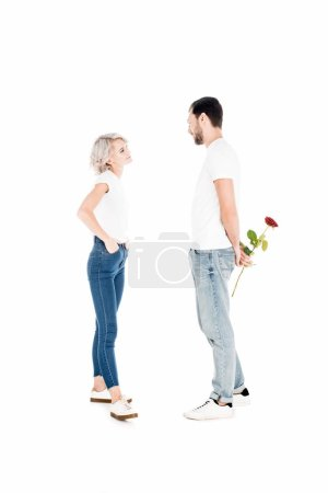 Beautiful couple looking at eahc other while man holding flower behind the back isolated on white