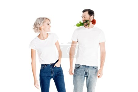 Beautiful couple looking at each other while man holding flower in mouth isolated on white
