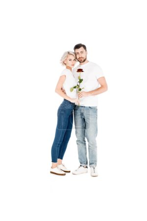Attractive young adult couple with flower hugging while looking at camera isolated on white