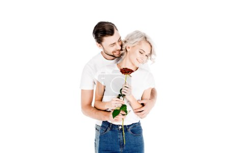 Beautiful young adult couple hugging while woman holding red rose isolated on white