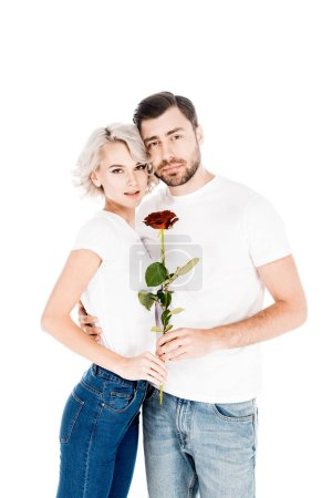 Beautiful couple with flower hugging while looking at camera isolated on white