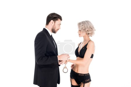 Handsome man handcuffed beautiful woman in lingerie while they are looking at each other isolated on white