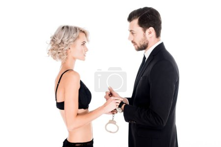 Couple of young adults holding handcuffs and looking at each other isolated on white