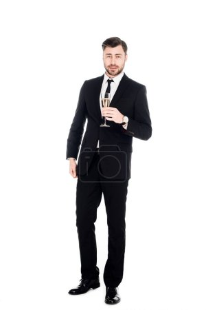 Handsome man in black costume with glass of champagne isolated on white