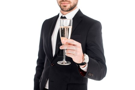Partial view of man in black costume holding glass of champagne isolated on white