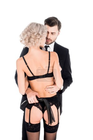 Handsome man with whip hugging blonde seductive woman in lingerie isolated on white