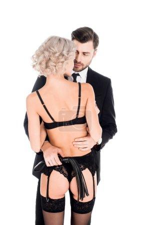 schöner Mann mit Peitsche umarmt blonde verführerische Frau in Dessous isoliert auf weiß