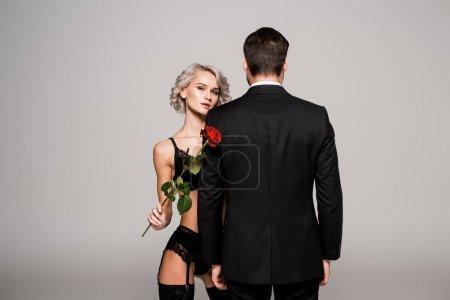 Photo pour Femme séduisante en lingerieavec rose rouge près de l'homme en costume noir isolé sur gris - image libre de droit