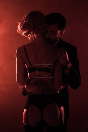 Man hugging seductive man in wonderful lingerie on red smoke background