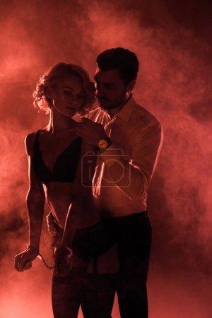 Couple passionné étreindre tandis que la femme est en menottes et séduisante lingerie sur fond de fumée rouge