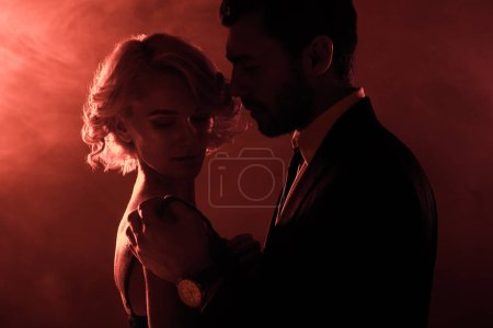 Passionate couple hugging on red smoke background