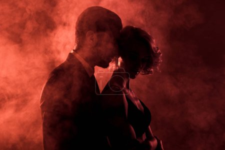 sensual man embracing passionate woman in smoke on red background