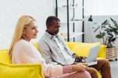 mature african american man using laptop while woman sitting on sofa with remote controller