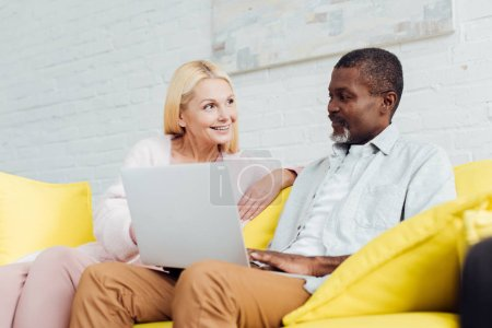 Photo for Happy woman sitting on sofa with african american man and using laptop - Royalty Free Image