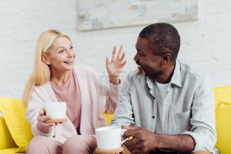 Photo for Emotional mature woman sitting on sofa and talking with african american man with white cups - Royalty Free Image